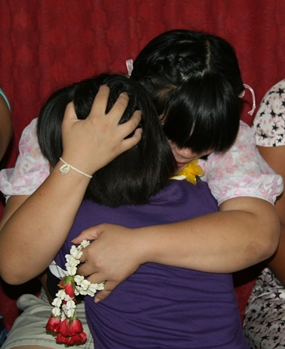 A teacher comforts one of the young girls at the Children's Home.