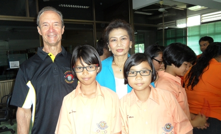 """(From left) Lewis """"Woody"""" Underwood and Nittaya Patimasongkroh with two proud schoolchildren who sport their new glasses."""