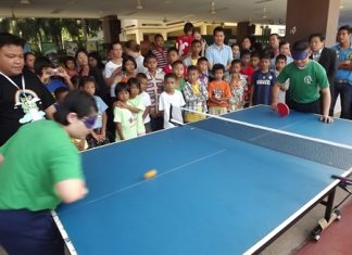 The crowd watches in awe as two students play a game of blindfolded table tennis.