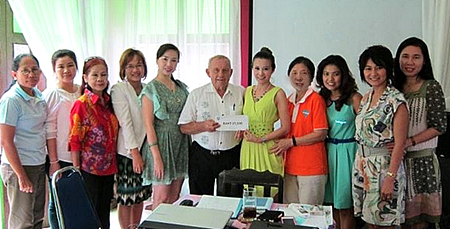 Jesters Care for Kids' Project Advisor Bernie Tuppin presents Praichit Jetpai, President of Pattaya YWCA, with funds to support this combined project.