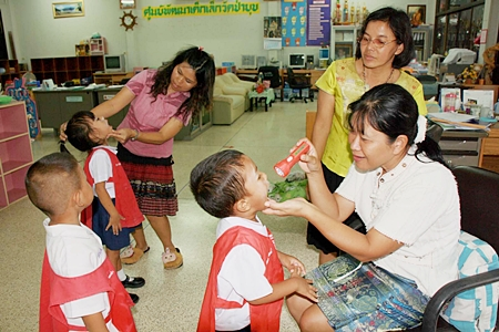 Administrators check young children for signs of hand, foot and mouth disease at the Ya Pa Yub Child Development Center in Khet Udomsak.  The center closed when 93 cases were discovered there.  Rayong thus far has been hardest hit by the outbreak, with 384 infected and 2 deaths.