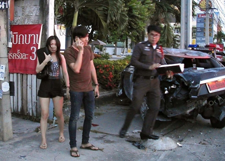 Alleged drunk driver Thanitpong Theppawat (on phone) and his allegedly equally drunk university student girlfriend stand by as police check the wrecked vehicle.