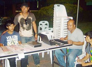 Police have arrested Saharat Phetnil (seated, left) for his involvement in a violent loan sharking ring.