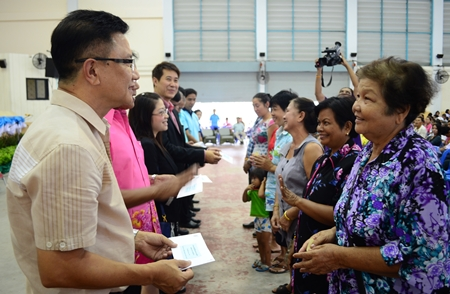 Deputy Mayor Wattana Chantanawaranon presents financial aid to Pattaya-area residents affected by flooding over the past year.