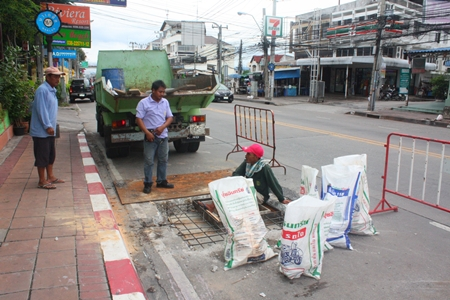Workers in Soi Naklua 16/1 fix the collapsed drainage lids.