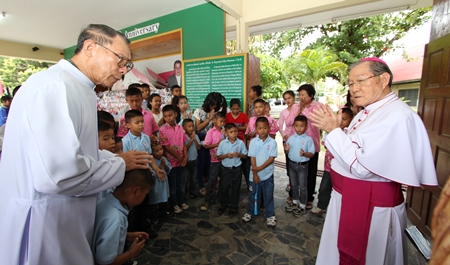 Father Veera Phangrak (left), director of the Pattaya Orphanage, along with children and care givers greet Bishop Emeritus Thienchai Samanjit (right).