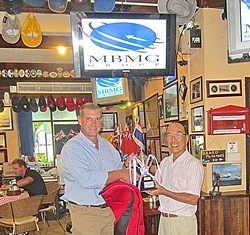 Simon Philbrook, left, presents the 'MBMG Golfer of the Year' trophy and prize to Mashi Kaneta.