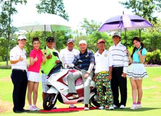 Burin Chanrakkankha, Club President Lions Club Pattaya, left, and Sithichai Sirisuthiworanant, President of the Sattaya Golf Association, pose for a photo with golfers and the prize motorcycle for a hole in one on the 4th hole.
