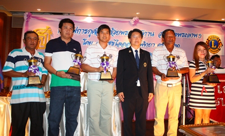 Burin Chanrakkankha, centre, stands with the tournament winners as they parade their trophies.