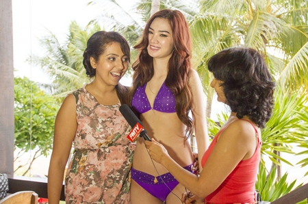 Sharan (left) of SiSi Bangkok talks to PMTV about her diamond and gold bikini worn by Miss Vietnam.