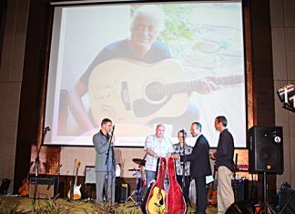 "Jimmy Page ""looks down from above"" as Ronny Gorrie collects his great auction prize, a Jimmy Page signed guitar. The legendary guitarist from Led Zeppelin donated his acoustic guitar inscribed with best wishes to Jesters Care for Kids, and included a beautiful case to protect it. After a year-long wait from last year's gala party night, the great success of this year's event proved well worth the wait."