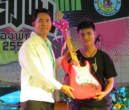 Mayor Itthiphol Kunplome (left) presents the outstanding guitarist award to Thummarat Uyatrakul from Awaken (right); an electric guitar from Sound House Life and Studio Pattaya