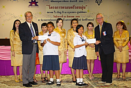 William Macey (left), charity chairman and Tony Oakes (right), president of the Pattaya Sports Club, present scholarships to youths.