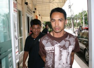 Police bring in Rangsiman Saengworanut for his alleged involvement in an ATM card theft.