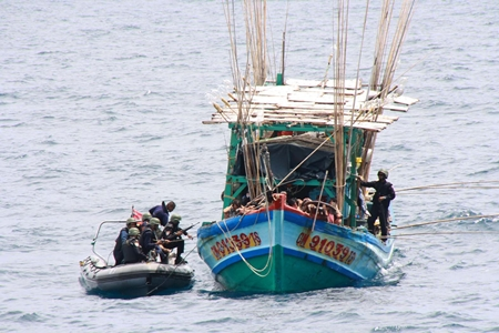 Enforcement officers from Royal Thai Navy patrol ships move in and secure a Vietnamese fishing boat caught illegally fishing in Thai waters.