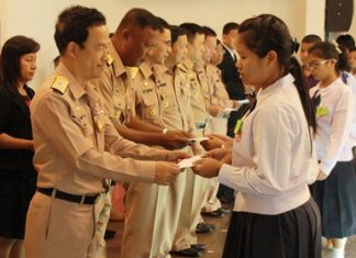 Students receive scholarship funds from Navy Savings Union officers.