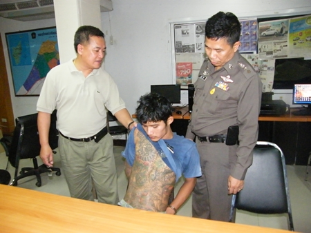 Police inspect the tattoos on suspected snatch thief Ekalak Chaemchoi.