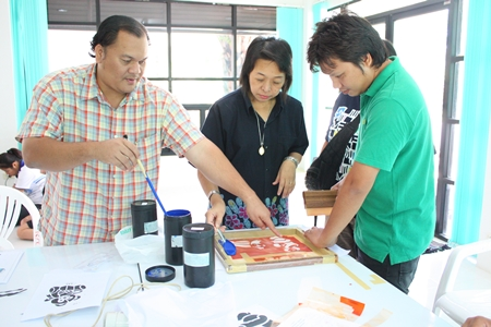 Wiroj Phadungket (left) and Wasana Changmuang (2nd left), experts on fabric printing, demonstrate techniques of coloring.