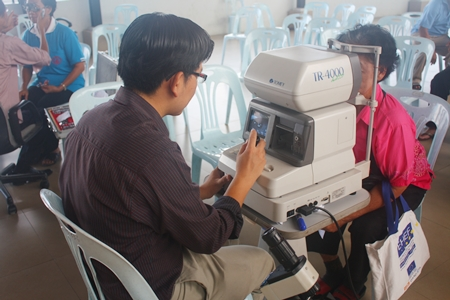 Elderly folks are given a follow-up eye check before being given their glasses.
