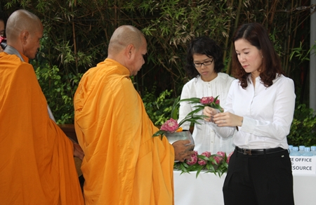 Sudachan Aprirattanapimonchai, Director of Finance & Business Support, leads employees to offer alms to monks at the Havana Bar & Restaurant.