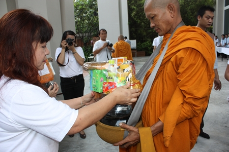 Darika Chaloeithoi, human relations director, leads employees to offer necessities to monks at the Holiday Inn Pattaya.