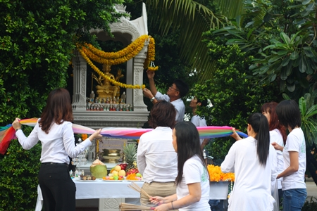 Employees pay homage to the Brahman shrine they use on the hotel grounds.