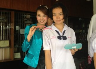 YWCA president, Praichit (Noy) Jetpai presents eyeglasses to a happy lady.