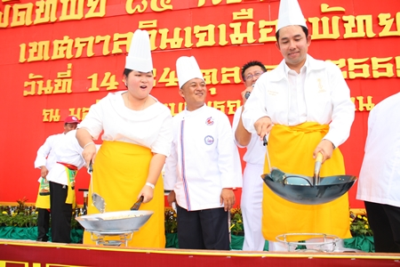 """Culture Minister Sukumol Kunplome (left) and Mayor Itthiphol Kunplome (right) stir up their versions of the """"Fried Rice in 85 Prosperous Pans""""."""