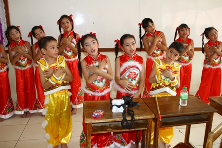 Students dressed in traditional Chinese outfits entertain the honored guests with song and dance.