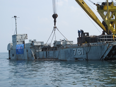 """A barge with heavy crane tows the HTMS Mataphon out to its new home off Koh Larn, were the ship was sunk to begin its new """"mission"""" as an underwater diving site near Koh Larn.  Officials said the sinking will help restore the marine ecosystem and be a place of knowledge for students, residents and tourists."""