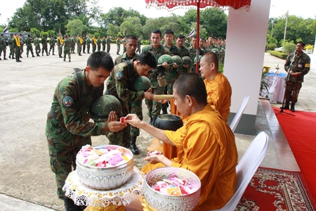 Monks bless the troops and hand out amulets for luck before the troops leave for the south.