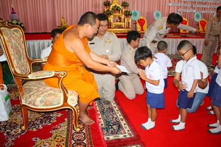 Pisanjariyaphiwat and officials present scholarships to students from Wat Chaiyamongkol nursery.