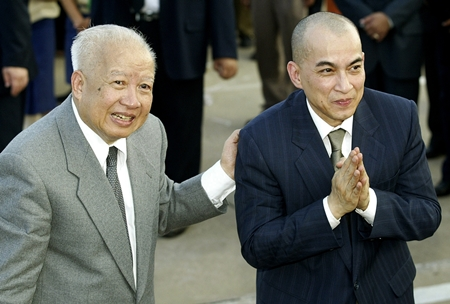 In this Oct. 20, 2004 file photo, Cambodia's King Norodom Sihanouk, left, introduces his son and successor, King Norodom Sihamoni upon their arrival at Phnom Penh airport, in Cambodia. (AP Photo/Andy Eames, File)