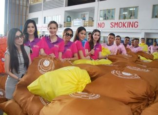 Miss Tiffany Universe pageant winners help Royal Thai Navy personnel pack bags of emergency rations.