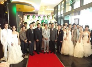 Honored guests pose with the models after the wedding dress fashion show at the Tsix5 Hotel.