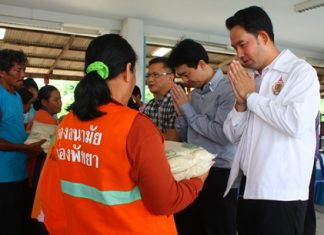 Mayor Itthiphol Kunplome (right) and Chonburi MP Poramet Ngampichet (2nd right) hand out rice to city workers.