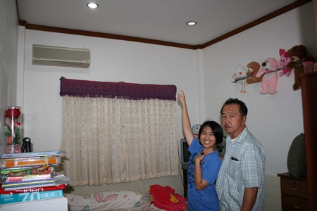 Happy she wasn't killed, Raphatsorn points to the ceiling where the bullet entered through her roof.  Her father doesn't look so amused.