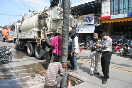 City officials inspect storm drains in Naklua as workers use heavy equipment to clear them of debris that might inhibit water flow during heavy rainfall.