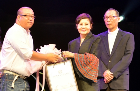 Suttikorn Jearpaittoon presents a bouquet and a gift of appreciation to Sopin Thappajug as father Michael looks on.