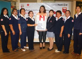 Aisika Songserm (center) poses for a group photo with members of the Banglamung Red Cross led by Nuanjan Saeng-Uthai (4th from left), and Phanisra Sukhjinda (4th from right) during the blood donation event.