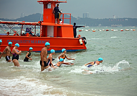Swimmers begin the 1.2 km competition in heavy rain.