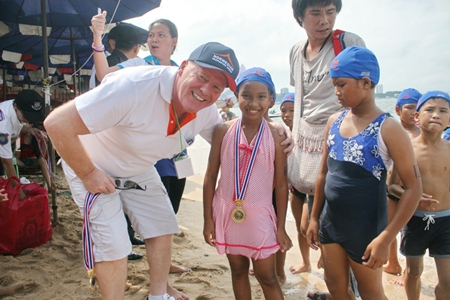 Rotary Jomtien-Pattaya PP Gudmund Eiksund presents medals to children competing in the Fun Swim for families, children and youths.