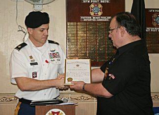 Commander Eric Larsen presents Major Daniel Robinson with a certificate of appreciation.