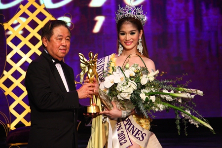 Senator Sutham Phanthusak, MD of the Tiffany Show Pattaya, presents the championship trophy to Kevin Balot, Miss International Queen 2012.