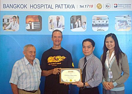 "(L to R) Bernie Tuppin and Lewis ""Woody"" Underwood present a certificate of thanks to Neil Maniquiz, head of Bangkok Hospital Pattaya's International Marketing and his deputy, Janya Rattanaliam."