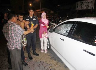 Police struggle to restrain Ayoub as the victim points out the damage he caused to her car.