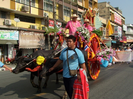 Sonthaya Kunplome and friends ride through the streets of Chonburi at the head of the opening day parade on a fabulously decorated buffalo drawn cart. (Photo from CPRD)