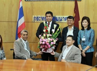 Suporntum Mongkolsawadi (seated right) and his committee presents flowers to Chatchart Sitthipan from the Ministry of Transport.
