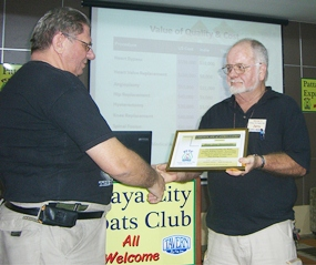 Board member Jerry Dean presents member Jon (Hans) Stroosnyder with a certificate recognising Jon's services to the club, particularly assisting members with monthly visits to the Motor Registry to get licences and car registrations.