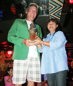 Ross Schiffre wears the champion's green jacket as he receives the winner's trophy from Mamasan Ead.
